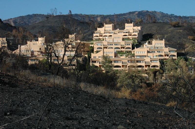 N&aring;gra bostadsomr&aring;den har helt omg&auml;rdats av branden.<br /><br />---<br /><br />Algunas urbanizaciones se vieron completamente rodeadas por el fuego.