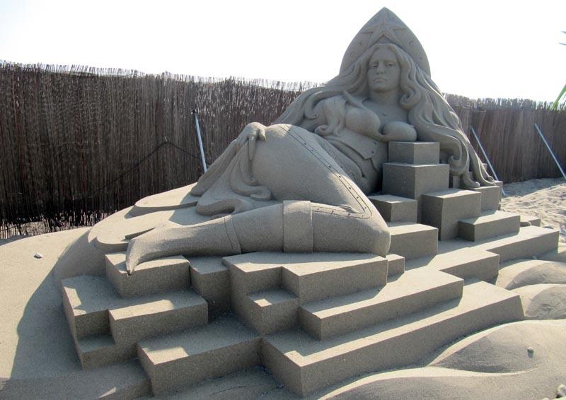 Sandskulptur som verkar iaktta betraktaren.