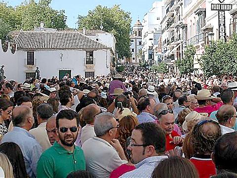 """Tjurfäktarekipagen anländer traditionellt i hästdroskor via gatan """"Virgen de la Paz"""", där en stor folkmassa hoppas få en skymt av matadorerna."""