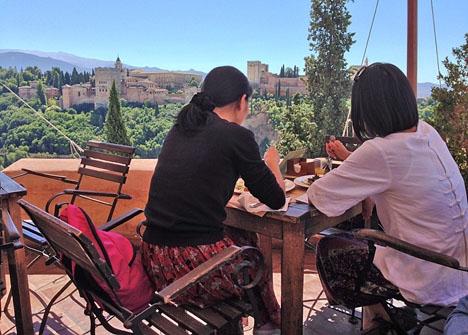 Två turister njuter av en lunch i Granada med Alhambra som utsikt.