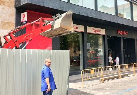 En grävskopa ser nästan ut att vara redo att riva en filial till Banco Popular. Riktigt så illa är dock inte situationen, åtminstone inte för spararna.