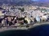 Flygvy över centrala Marbella, med Hotel El Fuerte i rosa vid strandpromenaden och gamla stan ovanför.