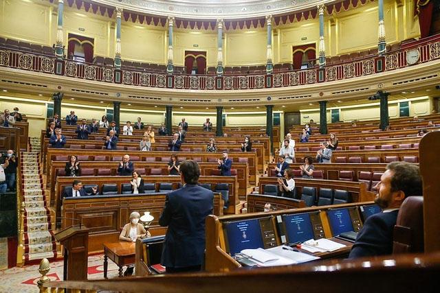 Ministrar och ledamöter för PSOE och Unidas Podemos applåderar regeringschefen Pedro Sánchez i parlamentet 3 juni, inför oppositionsledaren Pabo Casado (PP), till höger. Foto: PSOE