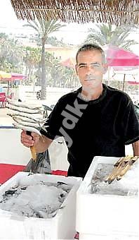 """Manuel Galiana är """"espetero"""", det vill säga ansvarig för grillningen av sardinspetten i den lilla båten fylld av sand."""